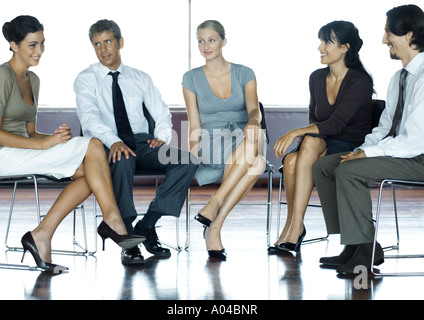 Businesspeople sitting in chairs having meeting, full length - Stock Photo