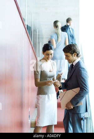 Executives standing, speaking and exchanging business card - Stock Photo