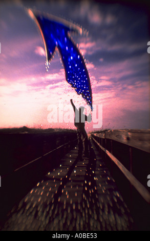 Graphic image of a silhouette of a man jumping on a road with a large blue arrow pointing upward toward the sky - Stock Photo