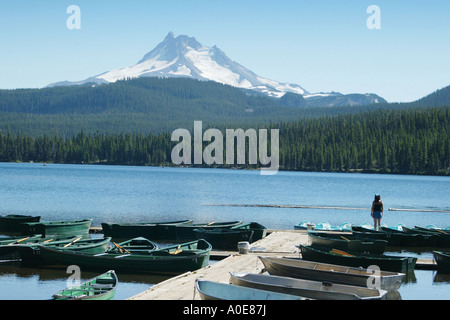 A young woman standing on the dock at Olallie Lake gazing at Mt Jefferson in the distance - Stock Photo