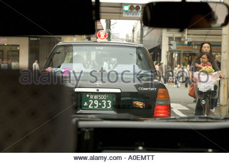 mother with child cycling through the narrow streets of Kyoto seen from inside a car - Stock Photo