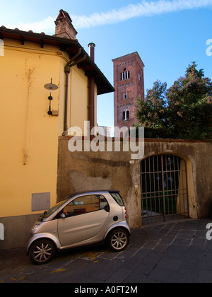 Metallic grey silver Smart car parked in typical street in Lucca Tuscany Italy - Stock Photo