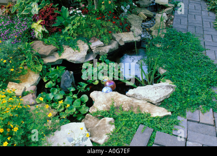 Small decorative fish pool with fountain waterfall in landscaped garden with brick paths and patio,  Midwest  USA - Stock Photo