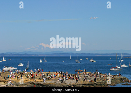 Crowd watching Canadian forces Snowbirds aerobatic team performing over Mt. Baker and Juan de Fuca Strait on warm - Stock Photo