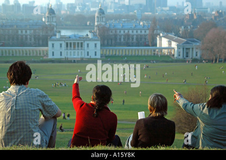 Horizontal landscape of tourists enjoying the view over Greenwich Park, pointing out landmarks on the horizon. - Stock Photo