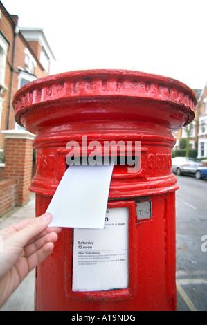 posting letter in UK Postbox - Stock Photo