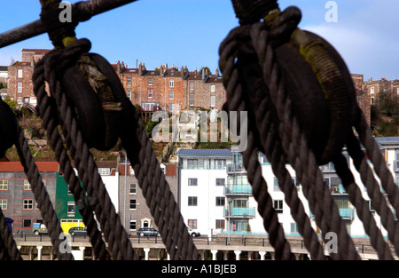 Modern apartment building viewed through rigging of SS Great Britain on quayside Bristol docks England UK - Stock Photo