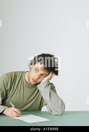 Young man writing, leaning on elbow and looking away - Stock Photo