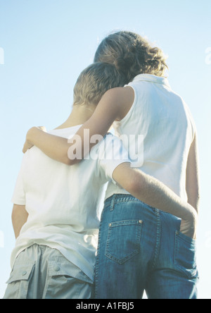 Boy and girl standing side by side with arms around each other - Stock Photo