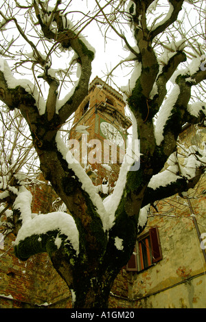 A clock tower is captured by snow covered branches like a metaphor for the end of life Umbria Italy - Stock Photo