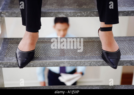 Low section view of a person standing on a staircase and a young man reading a newspaper in background - Stock Photo