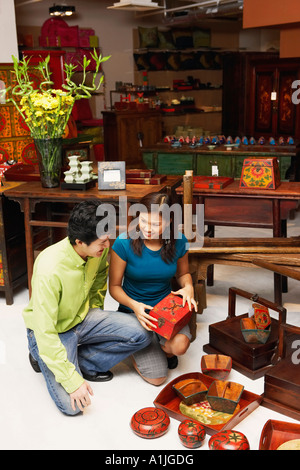 High angle view of a young man and a young couple choosing merchandise in a store - Stock Photo