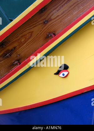 Maltese Luzzu brightly coloured wooden fishing boat with osaris - Stock Photo