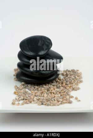 Stack of black stones on gravel - Stock Photo