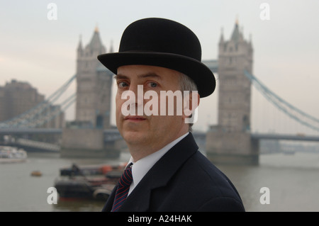 Traditional English city gent in suit and bowler hat by Tower Bridge, City of London, UK. - Stock Photo