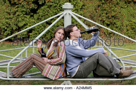 Girl and Boy Drinking in Park - Stock Photo