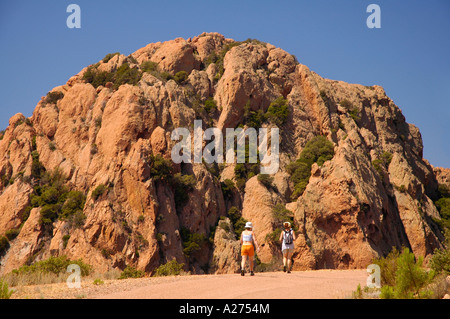 Trekkers walking in front of massive rocky cliff, Massif de l'Esterel, Cote d'Azur, Provence, France - Stock Photo