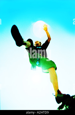 Male age 20-25 rock jumping, the Image is color and shot from below. - Stock Photo