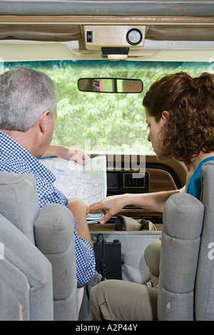 Couple planning trip with a map in caravan - Stock Photo