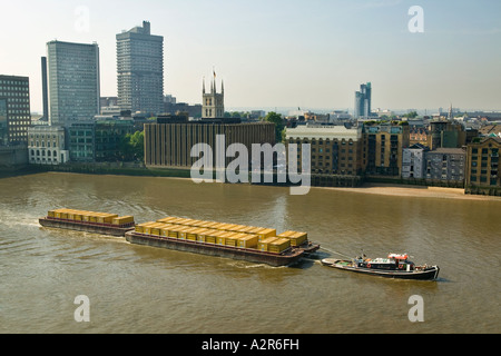 tug boat pulls barge of containers up river Thames London - Stock Photo