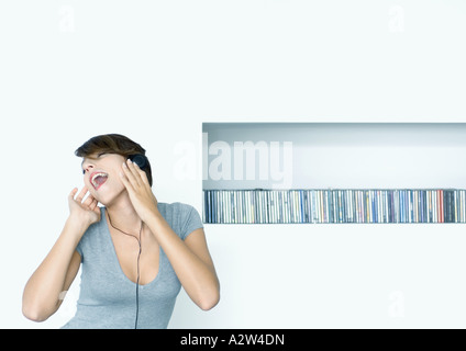 Woman listening to headphones, shelf of cds in background - Stock Photo