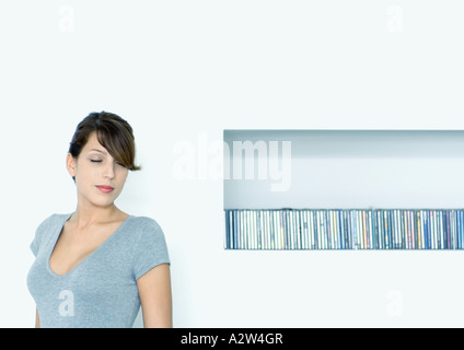 Young woman next to shelf of CDs - Stock Photo