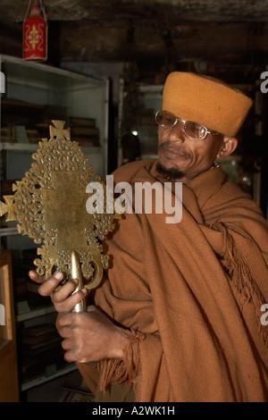 Monk showing old 1674 Lalibela cross in museum of Kebran Gabriel or Kibron Gebriel orthodox christian monastery - Stock Photo