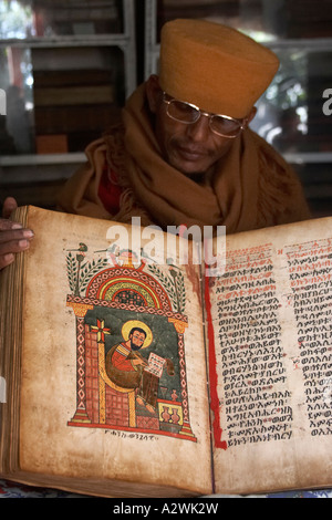 Monk showing old 1555 illuminated manuscript parchment book of gospels in museum of Kebran Gabriel monastery on - Stock Photo