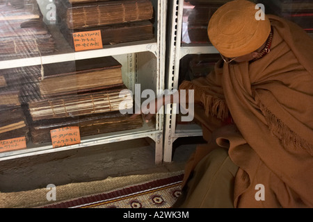 Monk showing old 1313 bible in museum of Kebran Gabriel christian monastery on Lake Tana Ethiopia Africa - Stock Photo