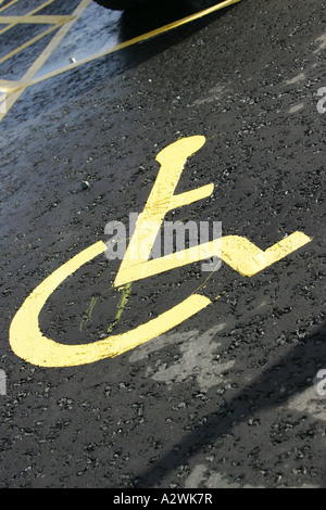 yellow freshly painted disabled sign on tarmac parking space on wet ground Belfast International Airport vertical - Stock Photo