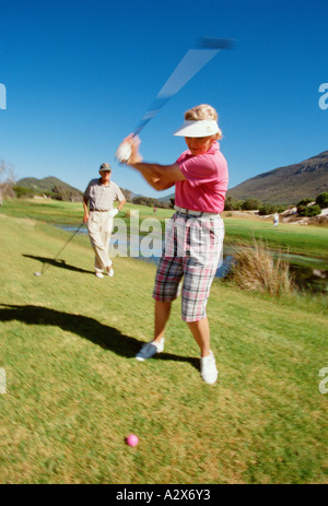 Retirement age couple playing golf. - Stock Photo