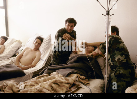 Socolitz, Bosnia, Sept 1992: a wounded Bosnian Serb soldier under treatment in Socolitz  hospital is helped by two - Stock Photo