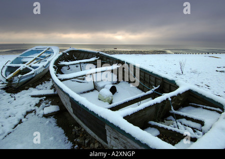 Snow on two fishing boats on Worthing beach after winter storms in Sussex and Kent in Southern England - Stock Photo