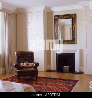 view of a fireplace and leather armchair in a bedroom - Stock Photo