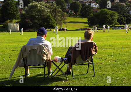 Older couple watching village cricket Portishead Bristol Avon England - Stock Photo