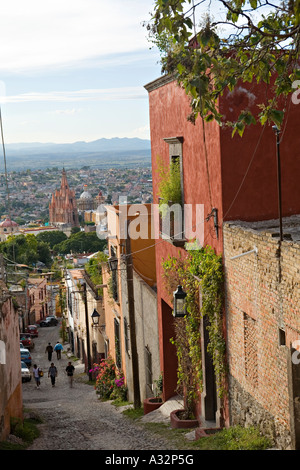 MEXICO San Miguel de Allende View from hilll down narrow street with pedestrians to Parroquia in center of downtown - Stock Photo