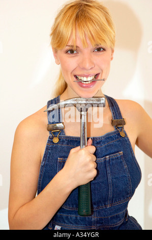 Junge Heimwerkerin in Latzhose mit Hammer und Nagel, young DIY woman in overalls with hammer and nail - Stock Photo