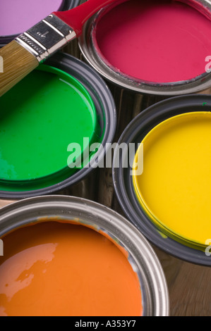 Cans full of colored paint with brush - Stock Photo