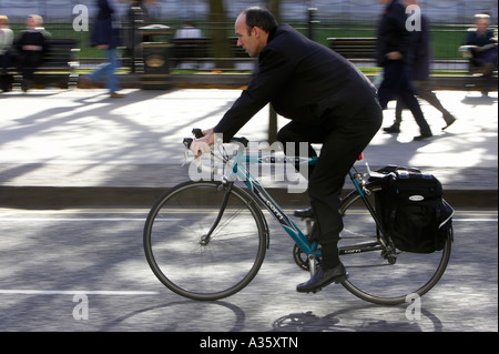 balding man cycling past on old style racing bike with saddlebags on road in a city centre - Stock Photo