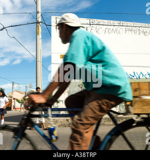 bicycle man white wall mexican urban street scene No model release required face away from camera blur crop so unrecognizable - Stock Photo