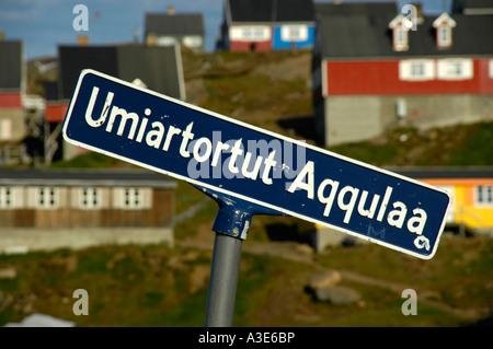 Road sign Umiartortut Aqqulaa colourful houses in settlement Ammassalik Eastgreenland - Stock Photo