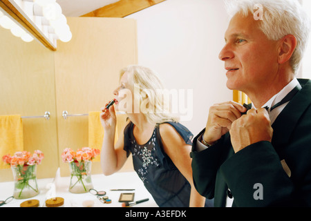 Side profile of a mature couple dressing up in the bathroom - Stock Photo