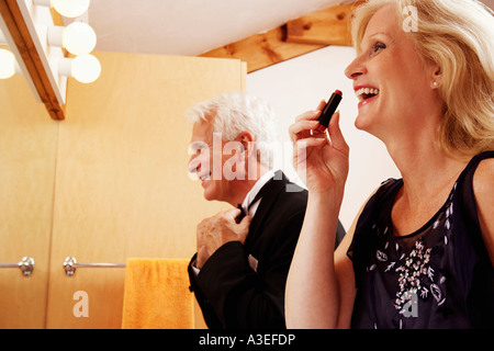 Close-up of a mature couple dressing up in the bathroom and laughing - Stock Photo