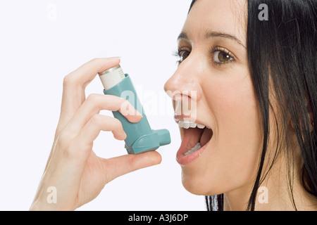 Woman using inhaler - Stock Photo