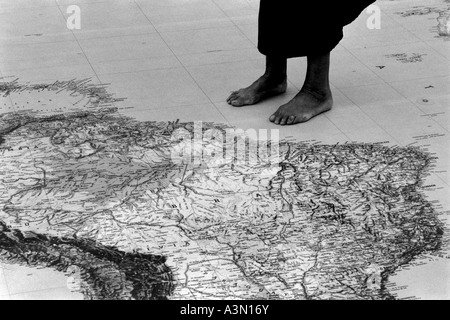 Immigrant standing close to a giant world map - Stock Photo