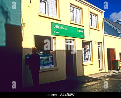 EYERIES COUNTY CORK REPUBLIC OF IRELAND September Woman posting letter in post box at village Post Office - Stock Photo