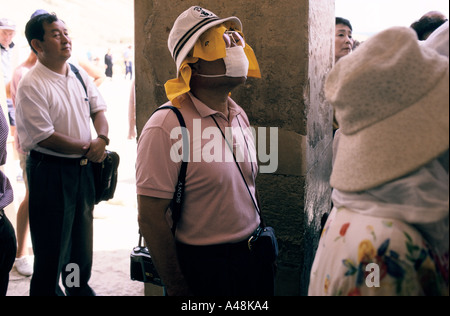 A japanese tourist wearing a face mask and vizor at the temple of hateshput in the valley of the kings - Stock Photo