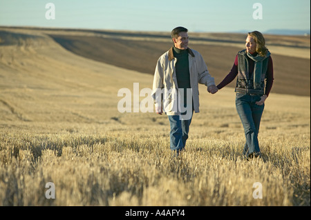 Couple walking through fields of cut grass in Fall Colorado early morning - Stock Photo
