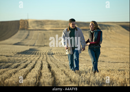 Couple smiling walking through fields of cut grass in Fall Colorado early morning - Stock Photo