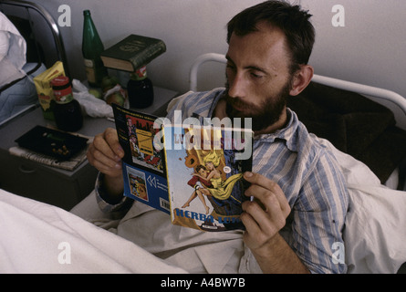 A wounded Bosnian Serb soldiers reads a comic book in his hospital bed,  Socolitz, Sept 1992 - Stock Photo